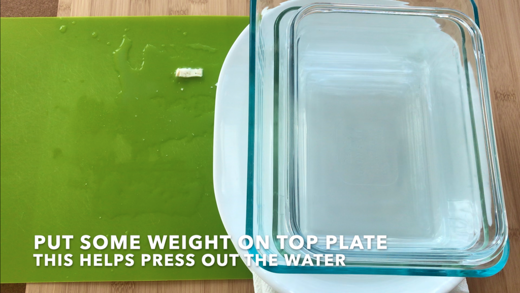 The weight 2-3 pyrex containers can help press out the water